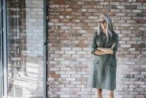 Улыбающаяся женщина с длинными седыми волосами стоит перед кирпичной стеной — стоковое фото