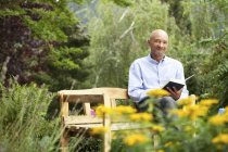 Senior man sitting on garden bench reading book — Stock Photo