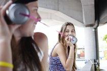 Two teenage girls using tin can phone — Stock Photo
