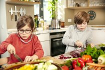 Boy and girl chopping vegetables in the kitchen — Stock Photo