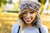 Portrait of smiling young woman wearing fur hat — Stock Photo