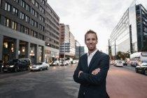 Porträt eines lächelnden Geschäftsmannes mit verschränkten Armen in der Stadt stehend — Stockfoto
