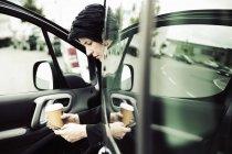 Businesswoman sitting in car, using smart phone — Stock Photo