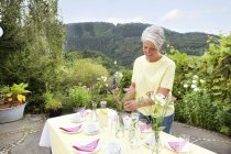 Mature woman decoration garden table for birthday party — Stock Photo