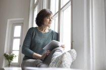 Женщина с планшетом смотрит в окно дома — стоковое фото