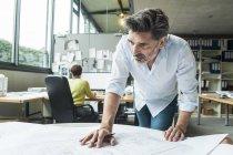 Architekten Grundriss im Büro mit Kollegen auf Hintergrund — Stockfoto