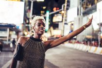 Young woman hailing taxi on Times Square at night, New York City, USA — Stock Photo
