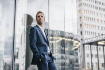 Retrato de empresário confiante encostado à fachada de vidro — Fotografia de Stock