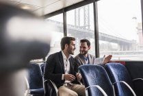 Two businessmen with document talking on passenger deck of a ferry — Stock Photo