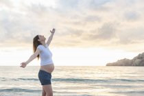 Happy pregnant woman standing on beach with arms outstretched — Stock Photo