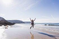 Девочка-подросток, прыгать от радости на песчаном пляже — стоковое фото