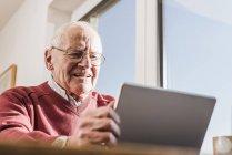 Hombre mayor sentado en casa y utilizando el ordenador portátil - foto de stock