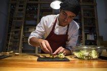 Man putting lettuce on mini hamburger buns — Stock Photo