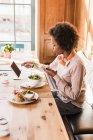 Молода жінка за допомогою мобільних телефонів і планшетних в кафе під час їжі — стокове фото