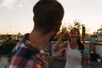 Junge Frau pustet Seifenblasen auf Dachterrasse, während ihr Freund sie beobachtet — Stockfoto