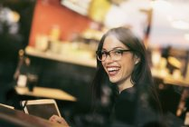 Portrait of laughing young woman sitting behind windowpane of a coffee shop with tablet — Stock Photo