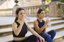 Due giovani donne sportive che si siede sulle scale bere da bottiglie — Foto stock