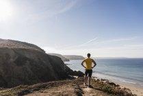 Sportive young man at the coast looking at view, france, crozon peninsula — Stock Photo