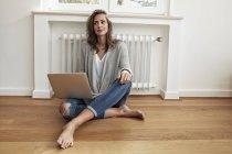 Улыбающаяся женщина сидит на полу с ноутбуком — стоковое фото