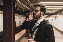 Joven hombre de negocios esperando en la plataforma de la estación de metro y usando smartphone - foto de stock