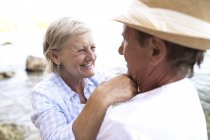 Active cute senior couple hugging together on beach — Stock Photo