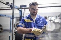 Reparador segurando pneu máquina de corte de piso na fábrica — Fotografia de Stock
