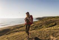 Блондинка Дівчинка-підліток з рюкзак, ходьба на березі моря у вечірні сутінки — стокове фото