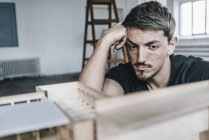 Serious architect looking at architectural model — Stock Photo