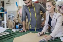 Fashion designer and tailor working together in workshop — Stock Photo