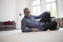 Расслабленный зрелый мужчина лежит на полу дома и смотрит в камеру — стоковое фото