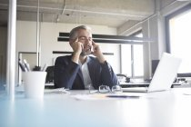 Businessman sitting with closed eyes at desk in office — Stock Photo