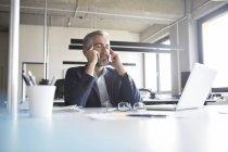 Empresário, sentado com os olhos fechados na mesa no escritório — Fotografia de Stock