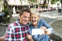 Happy cute senior couple taking selfie on smartphone — Stock Photo