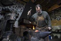 Blacksmith at in his workshop hammering metal detail — Stock Photo