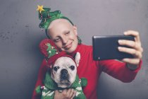Женщина с французским бульдогом делает селфи со смартфоном на Рождество — стоковое фото