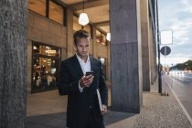 Businessman looking at smartphone in the evening — Stock Photo