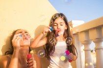 Девушка и ее младшую сестру, выдувания мыльных пузырей на балконе — стоковое фото