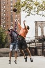 Two young men playing basketball on outdoor court — Stock Photo