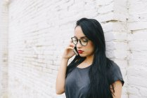 Young woman on cell phone in front of brick wall — Stock Photo