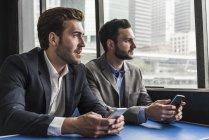Zwei Geschäftsleute mit Mobiltelefonen an Deck einer Fähre — Stockfoto