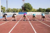 Женщины бегунов на тартан трек в исходное положение на стадионе — стоковое фото
