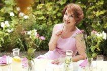 Ältere Frau im Garten sitzen, Geburtstagskarte schreiben — Stockfoto
