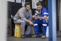 Two workers having a break looking at cell phone — Stock Photo