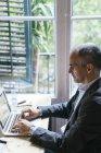 Homem de negócios sentado na mesa e trabalhando no laptop — Fotografia de Stock