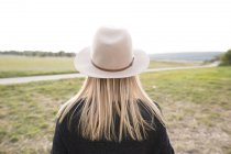 Rear view of woman wearing hat standing in countryside — Stock Photo