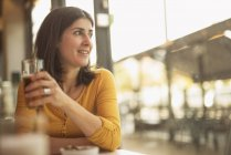 Smiling woman sitting in a coffee shop looking through window — Stock Photo