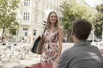 Smiling woman arriving at a sidewalk cafe looking at man — Stock Photo