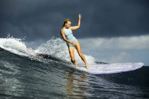 Indonesia, Bali, young sporty woman surfing in ocean — Stock Photo