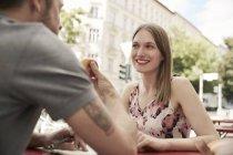 Lächelnde Frau Blick auf Menschen mit Apple in einem Straßencafé — Stockfoto