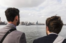 Two businessmen standing at East River, New York City, USA — Stock Photo